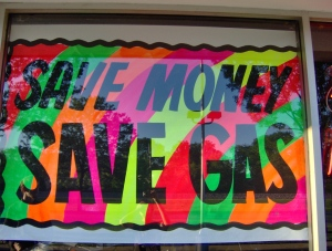 "A painted neon sign in Arlington Motor Sports storefront window reads in thick black letters, ""SAVE MONEY SAVE GAS."" Photo by Antonette Brotman."